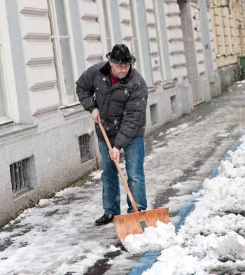 Mann der Schnee schippt vor dem Haus